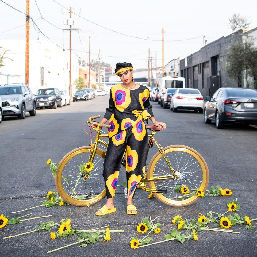 Portrait of Madame Gandhi with a bike and sunflowers around the Arts District.